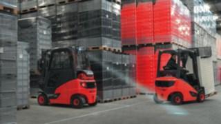 Vysokozdvižný vozík společnosti Linde sLED osvětlením jede ve skladu zboží snákladem