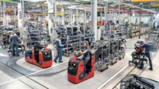 Tahač s několikavíceúčelovými přívěsy přepravuje díly na výrobní linku.