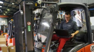 Technik s notebookem při kontrole vysokozdvižného vozíku k repasování