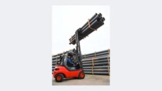 Vysokozdvižný vozík výrobní řady 351 od společnosti Linde Material Handling zvedá trubky.