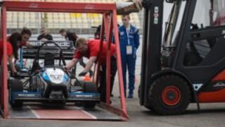 Pronajímaný vozík Linde zdvihá pomocí zvláštního zařízení závodní vůz